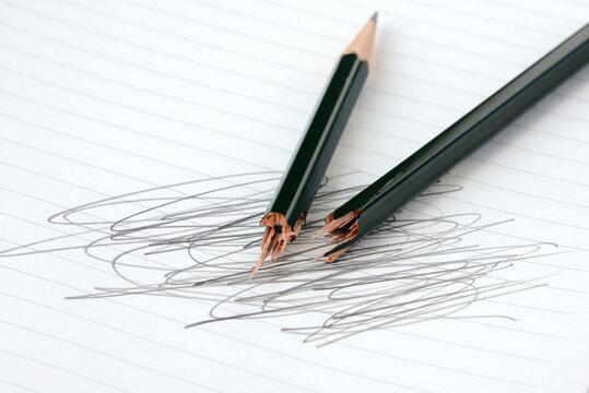 折られた鉛筆とぐちゃぐちゃ書きをされたノート