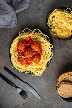 Top view of Spaghetti and Meatballs in back plate with cutlery and napkin. Traditional cuisine