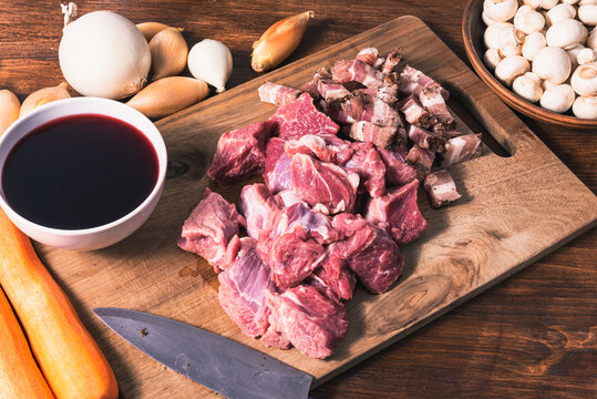 Ingredients for making burgundy beef: beef, shallots, carrots, bacon and red wine on a rustic-style cutting board table.