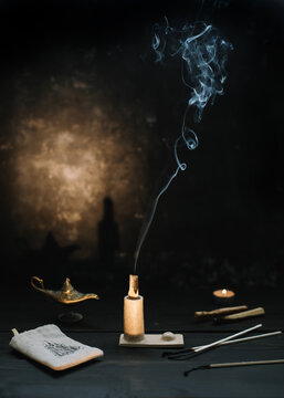 Palo Santo stick on fire with smoke in a beautiful candlestick. Healing, meditation, relaxation, purifying concept. Palo santo wood, Aromatic sticks on dark background. Cozy evening at home.