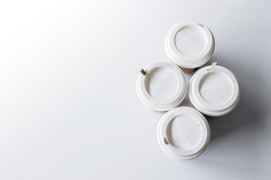 white cup of coffee on white table background. top view. flat lay