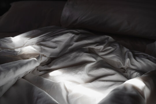 Close-up white blanket and pillow, on bed, with shade and shadow in the morning