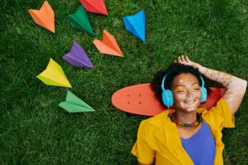Multi-ethnic woman wearing blue headphones listens to music lying on the grass near skateboard with...