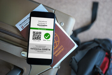 Fototapeta Disease immunity passport, Tourist uses of application on smartphone to show an international certification of vaccination at airport with Immunity passport and vaccination record card for covid-19 obraz
