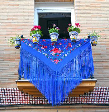 Andalusian balcony decorated for holding a festivity in the Triana district Sevilla Andalucia Spain. Blue Manila shawl and Triana ceramic pots with geraniums