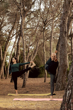 Couple practicing yoga and stretching in the middle of the forest.