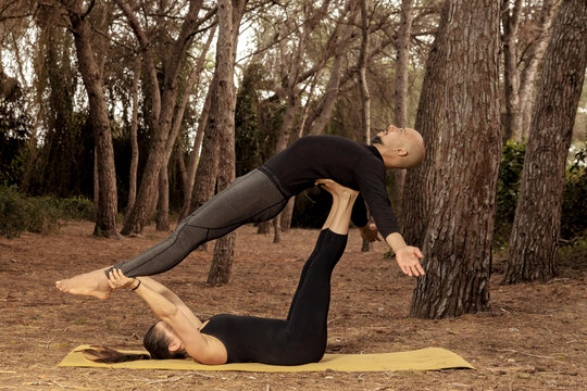 Caucasian woman does acroyoga with latin man, role reversal