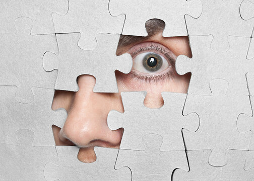 A person's face through the holes of the missing puzzles.