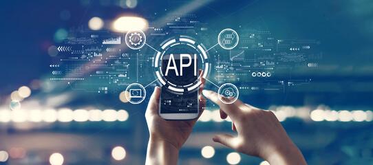 Fototapeta API - application programming interface concept with person using smartphone obraz