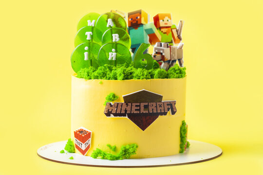 Kyiv, Ukraine - May 24, 2021: Birthday cake for a fan of Minecraft game on yellow background. Cake for a gameboy decorated with edible green grass