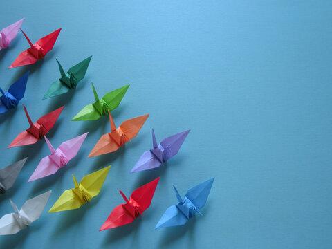 左下に集まるカラフルな折り鶴のグループと青背景のコピースペース