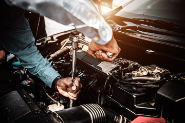 Obraz Car care maintenance and servicing, Close-up hand technician auto mechanic using the wrench to repairing change spare part car engine problem. Concepts of check and during periodic inspection service. - fototapety do salonu