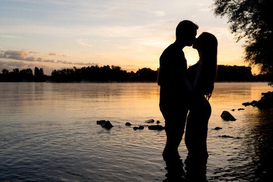 Silhouette eines jungen Paares im Sonnenaufgang am Flußufer