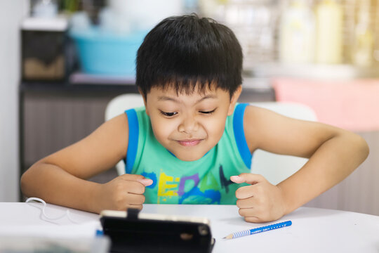 Distance learning online education. Asian boy student study with online video call teacher, studies at home and does school homework.