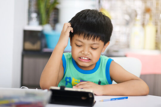 Distance learning online education. Asian boy student study seriously and crazy with online video call teacher, studies at home and does school homework.