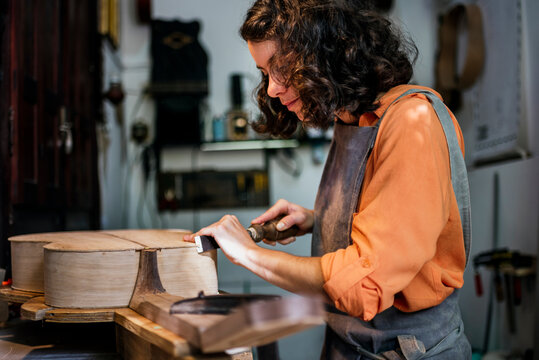 woman luthier making guitars in her musical instrument workshop