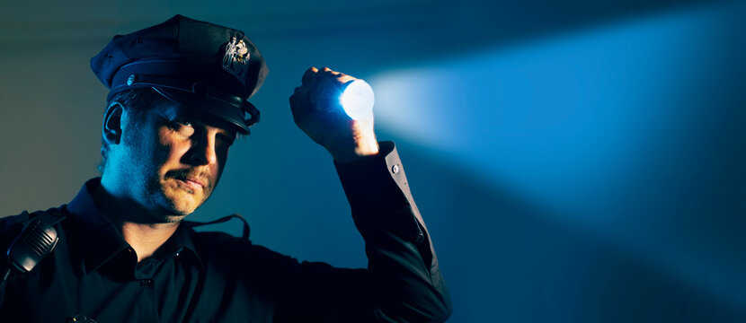 a police officer cop shines a flashlight during an investigation