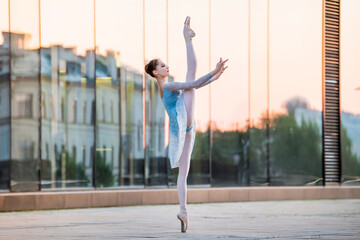 Fototapeta young ballerina dancing on pointe shoes against backdrop of the reflection of sunset in the city obraz