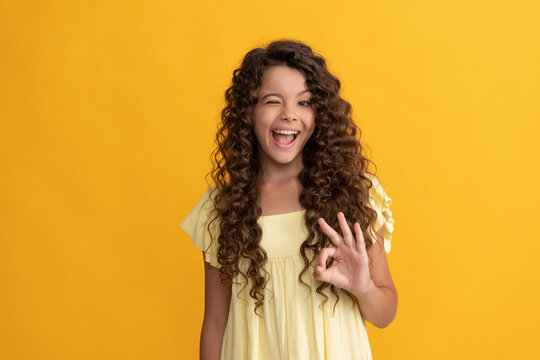 express positive emotion. haircare and skincare. hairdresser. ok. winking kid curly hair.