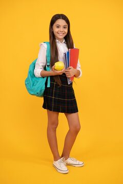 positive kid with backpack and workbooks hold apple lunch in school uniform full length, school.