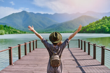 Fototapeta Traveler girl backpacker with open raised arms standing alone on pier and staring at lake and mountains. Enjoying free moment life and serene quiet peaceful atmosphere in nature. Back view obraz