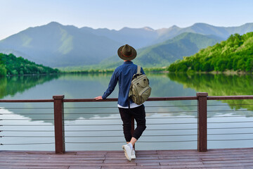 Fototapeta Hipster traveler backpacker standing alone on edge of pier and staring at lake and mountains. Enjoying beautiful freedom moment life and serene quiet peaceful atmosphere in nature. Back view obraz