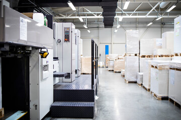 Fototapeta Printing shop or factory interior with modern offset paper machine and piles of sheets in background. obraz