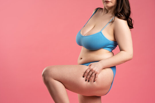 Fat woman with cellulite on thighs in blue underwear on pink background, body care concept