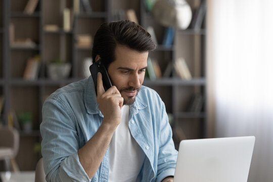 Concentrated young man holding phone call conversation, giving professional distant conversation to client, working on computer in modern home office, confident businessman multitasking during workday