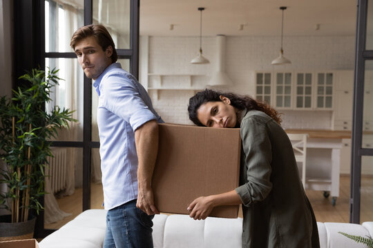 Tired millennial spouses exhausted of carrying heavy packages with belongings furniture at relocation day. Sad upset young family couple renters tenants leaving rented apartment when lease term is out