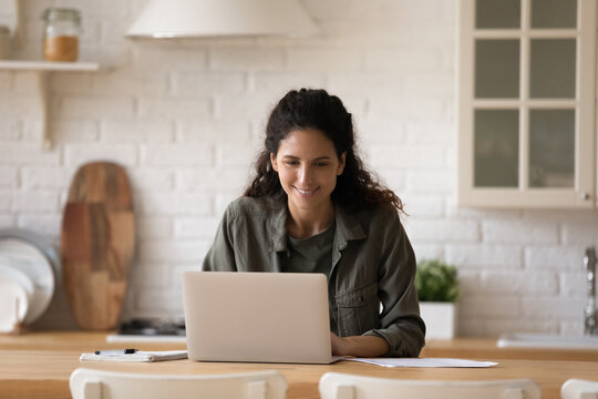 Young casual latin lady sit at kitchen table before laptop writing business email managing electronic documents. Busy millennial female expert freelancer working from home on startup project solution