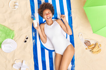 Fototapeta Emotional ethnic woman got sunburn on face exclaims loudly holds bottle of sunscreen wears white swimsuit poses on towel at beach sunbathes during summer day spends holidays near sea. Safe suntan obraz