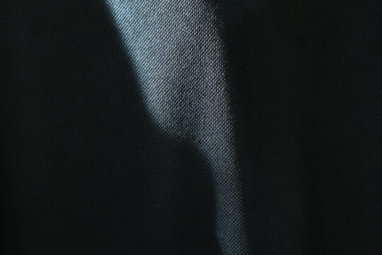 close up of sunlight spreading make shadow and shape on dark blue fabric background and texture