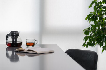 Fototapeta Notebook, cup of tea with teapot on table obraz