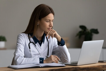 Serious medic professional, doctor, physician using laptop, giving online virtual consultation,...