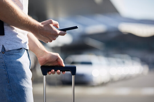 Man holding smartphone and using mobile app against a row of taxi cars. Themes modern technology, carsharing and travel.