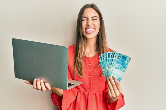 Young beautiful woman holding laptop and holding brazilian real sticking tongue out happy with funny expression.