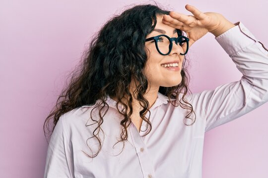 Young brunette woman with curly hair wearing casual clothes and glasses very happy and smiling looking far away with hand over head. searching concept.