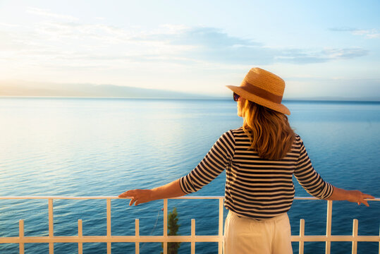 Rear view shot of a woman enjoying the sunrise and a perfect sea view while standing on the balcony
