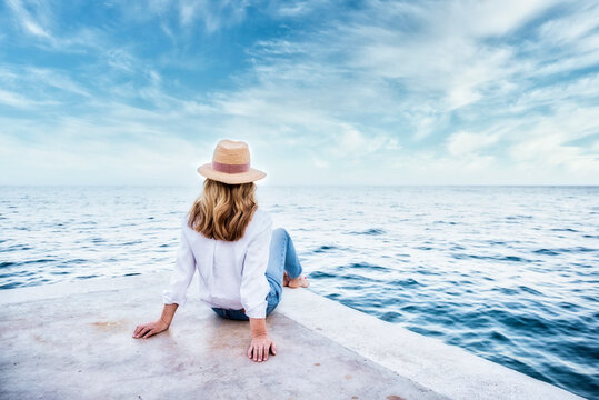 Rear view shot of a woman wearing straw hat and casual clothes while sitting on seaside and looking at the sea.