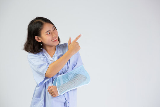 Broken arm girl in right arm sling thumbs up Woman showing pain from health care, broken arm and
