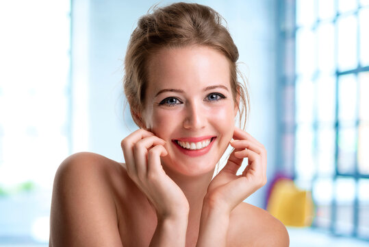 Close-up beauty portrait of gorgeous woman wearing perfect makeup while looking at camera and smiling at home