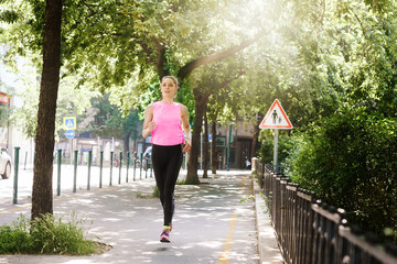 Obraz Full length shot of young woman wearing sportwear while running in the city.  - fototapety do salonu