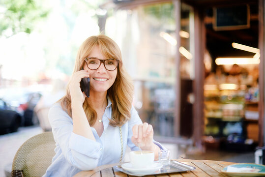 Middle aged woman sitting at the cafe and making a call
