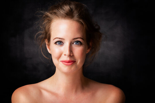 Close-up beauty portrait of gorgeous woman wearing perfect makeup while standing at isolated dark background