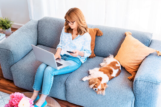 Shot of middle aged businesswoman using laptop and mobile phone while sitting on a couch at home and working from home. Her cute puppy relaxing next to her.