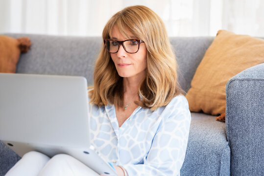 Shot of middle aged woman sitting in the living room on floor and using her laptop while working from home. Home office.