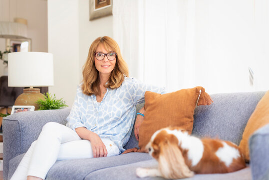 Shot of a happy middle aged woman with her cute puppy relaxing on sofa at home