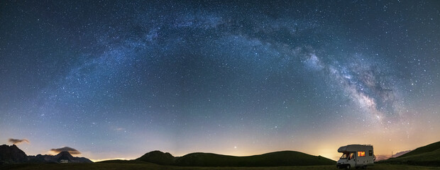 Obraz Panoramic night sky over Campo Imperatore highlands, Abruzzo, Italy. The Milky Way galaxy arc and stars over illuminated camper van. Camping freedom in unique hills landscape. - fototapety do salonu
