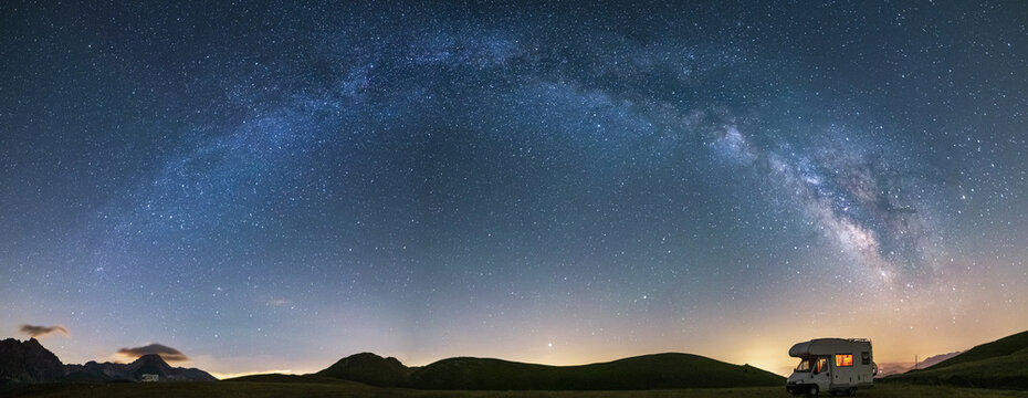 Panoramic night sky over Campo Imperatore highlands, Abruzzo, Italy. The Milky Way galaxy arc and stars over illuminated camper van. Camping freedom in unique hills landscape.